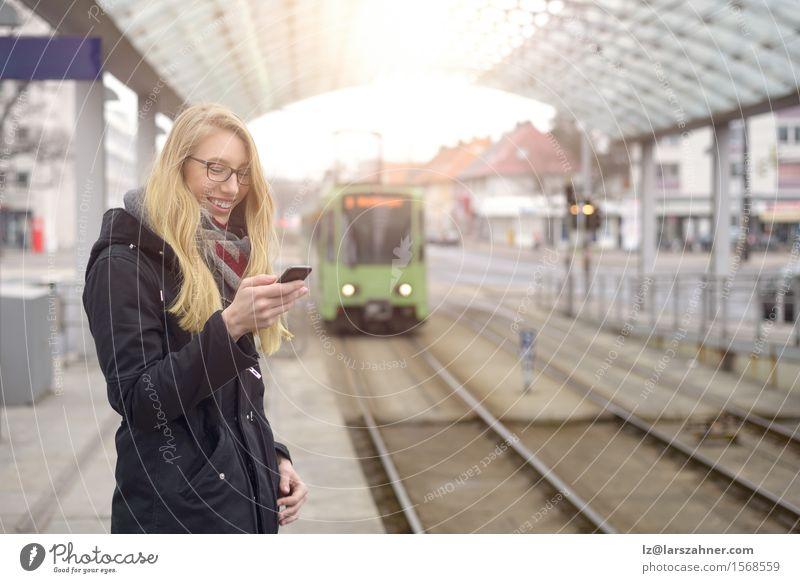 Junge Frau mit Handy an der Bahnstation Glück Ferien & Urlaub & Reisen Winter Telefon Erwachsene 1 Mensch 18-30 Jahre Jugendliche Verkehr Eisenbahn blond