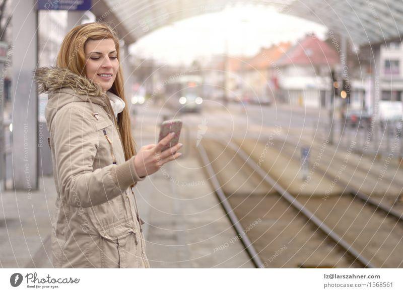 Junge Frau mit Handy an der Bahnstation Mensch Ferien & Urlaub & Reisen Jugendliche Winter 18-30 Jahre Erwachsene Glück Verkehr blond stehen warten Lächeln