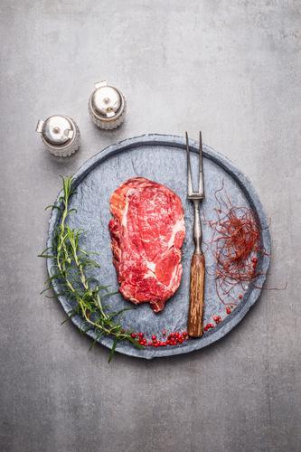 Ribeye Steak roh mit Gewürzen Lebensmittel Fleisch Kräuter & Gewürze Ernährung Mittagessen Abendessen Picknick Bioprodukte Teller Gabel Stil Gesunde Ernährung