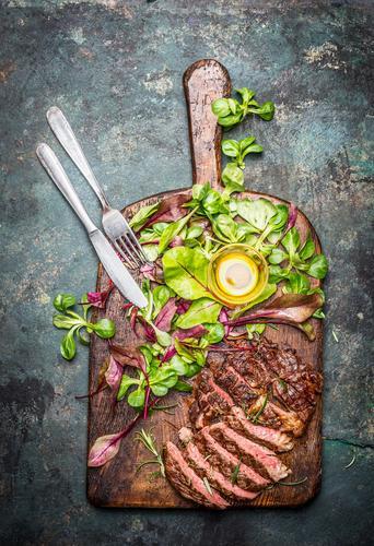 Grillsteak mit grünem Salat und Besteck auf Schneidebrett Gesunde Ernährung Speise Essen Foodfotografie Stil Lebensmittel Design Tisch Kräuter & Gewürze Fisch