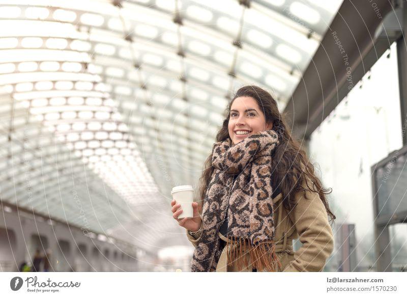 Lächelndes Braun im Wintermantel, der einen Tasse Kaffee hält Mensch Frau Jugendliche 18-30 Jahre Gesicht Erwachsene Glück Verkehr Textfreiraum authentisch