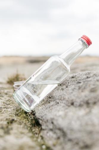 Die Flasche ist halb voll Getränk Trinkwasser Alkohol Spirituosen Glasflasche Schnapsflasche Felsen Stein stehen authentisch hell rot durchsichtig Neigung
