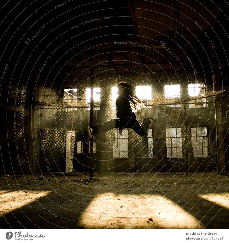 JUMP springen Aktion hoch Sonne Gegenlicht alt verfallen Fabrik Maschendrahtzaun Schatten Sonnenstrahlen fliegen Mann Extremsport dread Luftverkehr