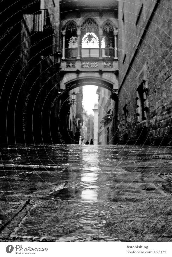 dunkle Gasse Stadt Straße dunkel grau Stein Schwarzweißfoto nass Tor Spanien Verkehrswege Katalonien Barcelona Gasse Altstadt