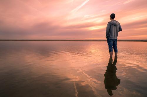 Den Blick in die Ferne schweifen lassen Mensch Natur Jugendliche Sommer Junger Mann Meer Erholung ruhig Strand Denken orange maskulin leuchten träumen Wellen