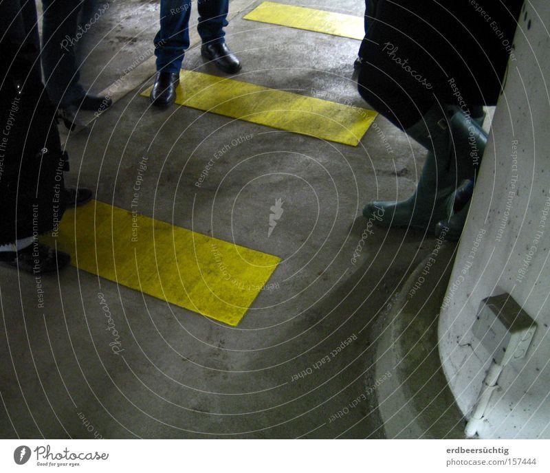 Meeting Verabredung Besprechung Mensch dunkel Schatten Tiefgarage grau gelb Zebrastreifen Kommunizieren Menschengruppe Fuß Beine