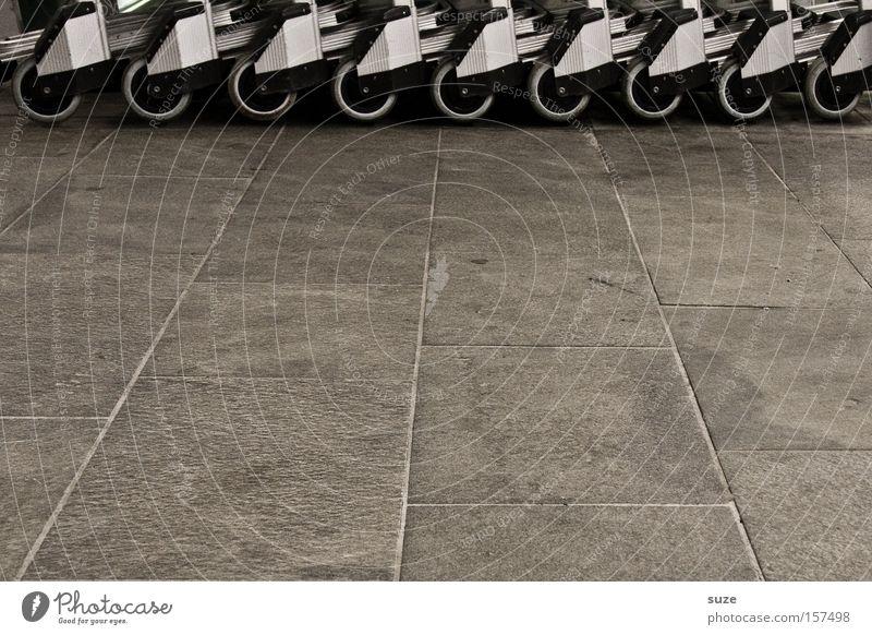 Rollenspiel Güterverkehr & Logistik Platz Flughafen grau Gepäck Wiederholung Kofferkuli Bodenplatten Rad Steinplatten Bodenbelag Steinboden Anschnitt Farbfoto