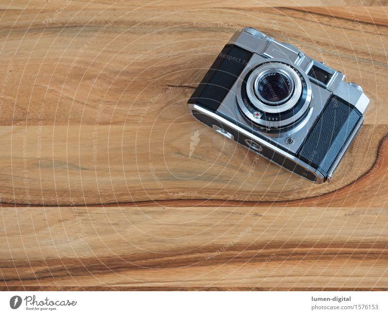 analoge Kleinbildkamera auf braunem Holztisch Fotokamera Technik & Technologie alt retro schwarz silber abbild Aussehen antik Gerät Hintergrundbild Blende