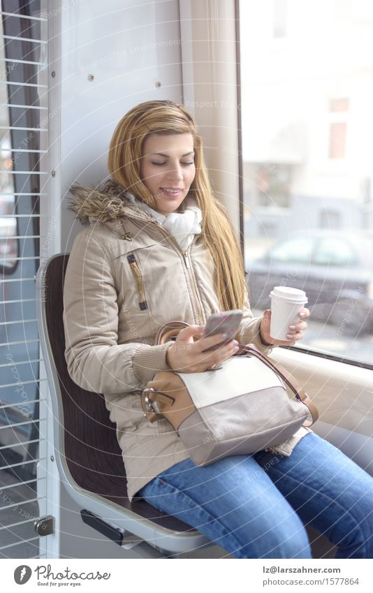 Blonde Frau, die auf Nahverkehrszug sitzt Kaffee Lifestyle Glück schön Winter Telefon Erwachsene 1 Mensch 18-30 Jahre Jugendliche Verkehr Eisenbahn Jeanshose