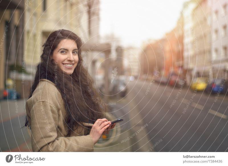 Brunettefrau, die an ihrem Handy simst Lifestyle Gesicht Business Telefon PDA Frau Erwachsene 1 Mensch 18-30 Jahre Jugendliche Herbst Straße brünett Lächeln