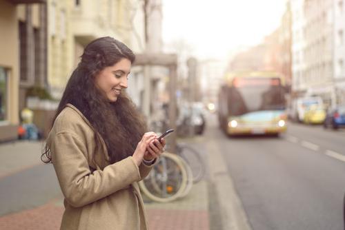 Brunettefrau, die an ihrem Handy simst Mensch Frau Jugendliche Stadt schön 18-30 Jahre Gesicht Erwachsene Straße Glück Business Verkehr Textfreiraum