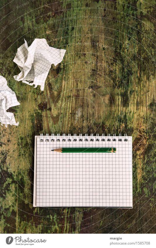 Einfallslos! Leere zerknüllte Notizblätter mit einem leeren Schreibblock mit karierten Papier und einen Bleistift auf einem alten Holztisch