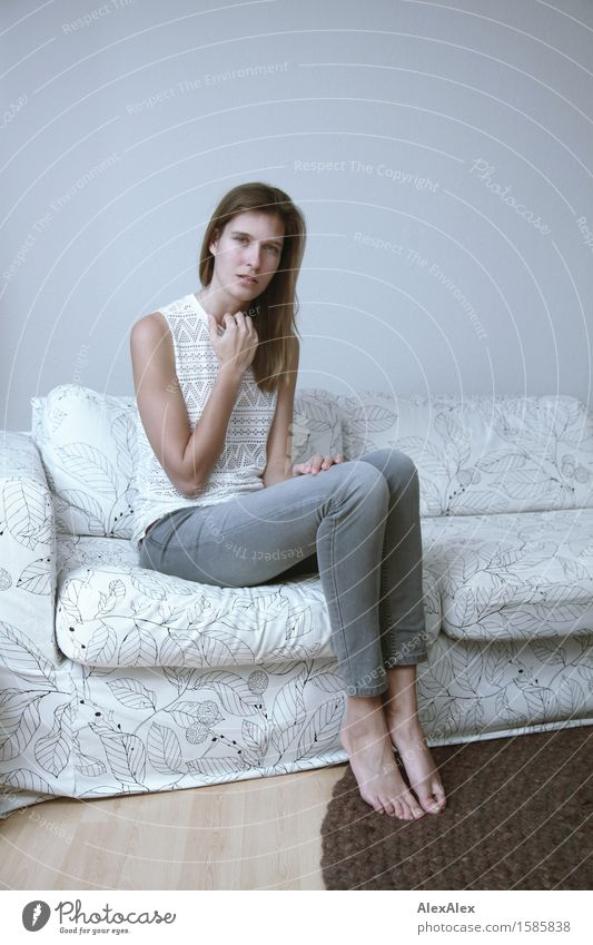 Erfahre mehr darüber elegant Sofa Raum Junge Frau Jugendliche Beine 18-30 Jahre Erwachsene Jeanshose Top Barfuß brünett langhaarig Blick sitzen ästhetisch