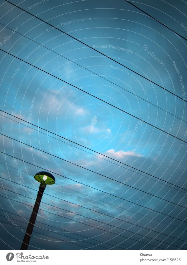 ,\\ Laterne Straßenbeleuchtung Strommast Kabel Stahlkabel Leitung Oberleitung Starkstrom Himmel Wolken blau Dämmerung Abend Linie Osten