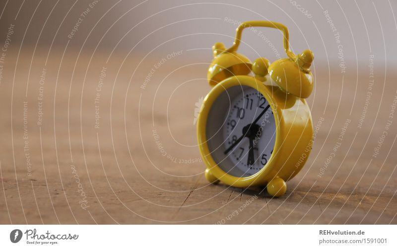 rund | um die uhr Uhr alt Geschwindigkeit Zeit Wecker Uhrenzeiger langsam gelb klein 6 aufstehen Frist Alarm Holz Tisch Farbfoto Innenaufnahme Detailaufnahme