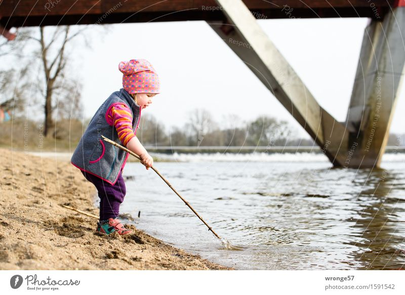 Spielen am Fluss Kind Kleinkind Mädchen Kindheit 1 Mensch 1-3 Jahre Flussufer Strand Elbe Wasserfall nass braun grau Freude spielend Brücke Sandstrand Freiraum