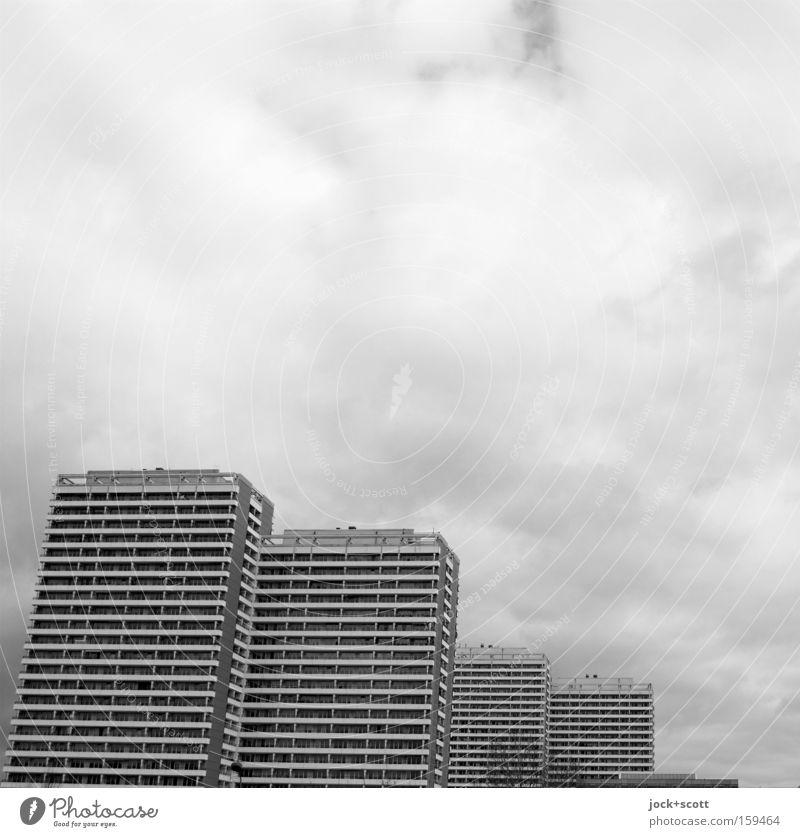 kuscheln in Marzipanien Haus Wolken schlechtes Wetter Marzahn-Hellersdorf Hochhaus Fassade Beton Plattenbau Reihe hintereinander Block DDR Schwarzweißfoto