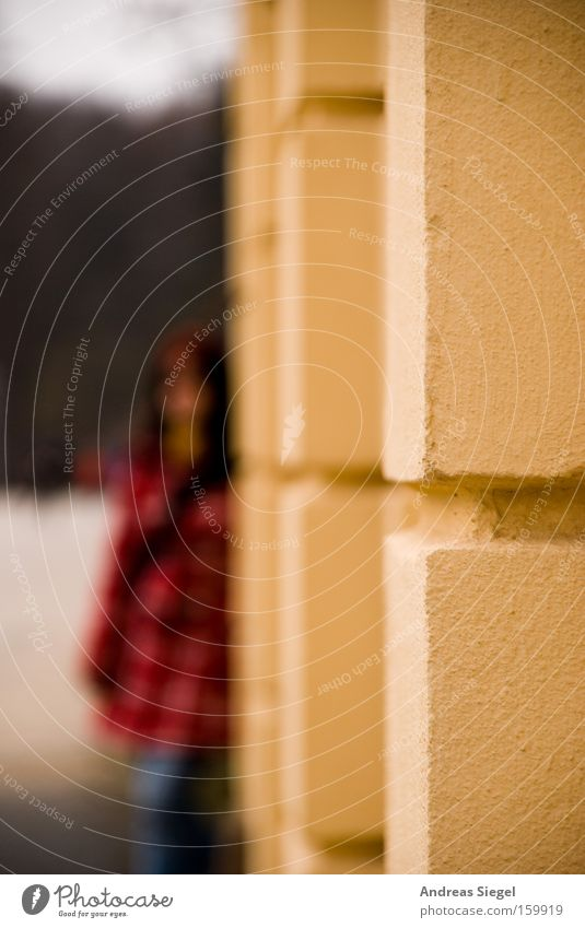 An der Ecke Frau rot Haus Wand Stein Mauer Jacke verstecken Tiefenschärfe