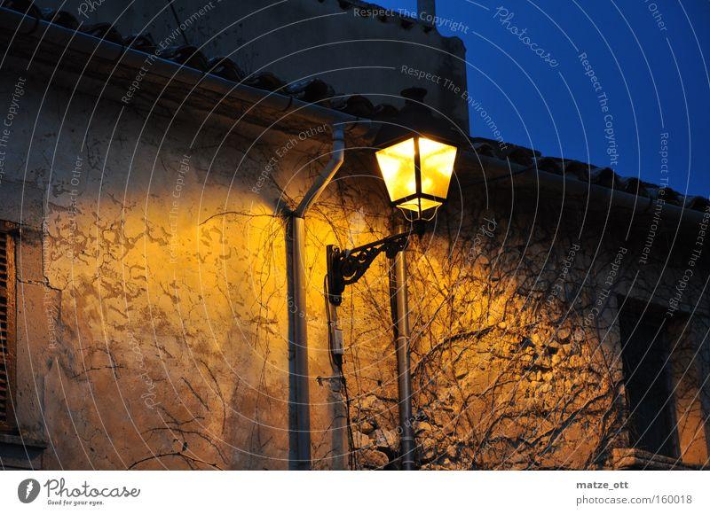 warmes Licht in der Dämmerung Straßenbeleuchtung Laterne Nacht Abend Abenddämmerung dunkel Haus Stadt Dorf Mallorca Spanien historisch Detailaufnahme