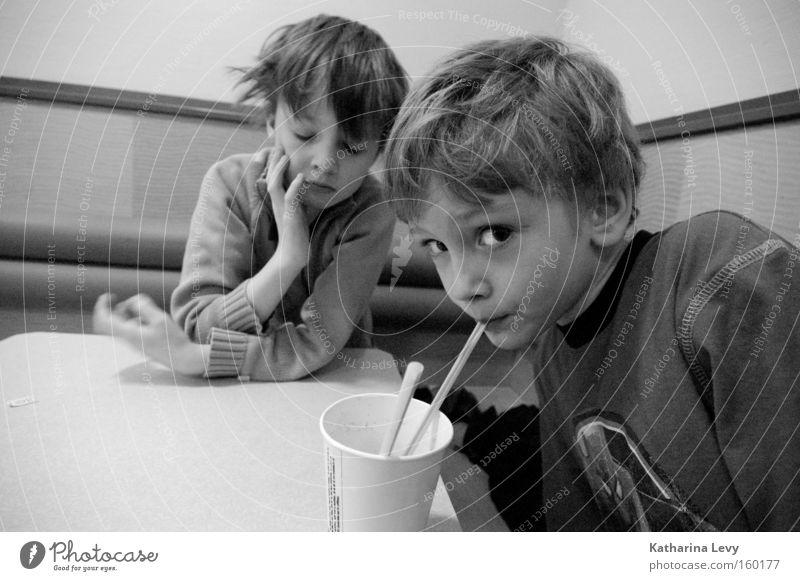 Fast Food Schwarzweißfoto Innenaufnahme Zentralperspektive Weitwinkel Blick in die Kamera Getränk trinken Becher Trinkhalm Kind Mensch Junge Kindheit 2
