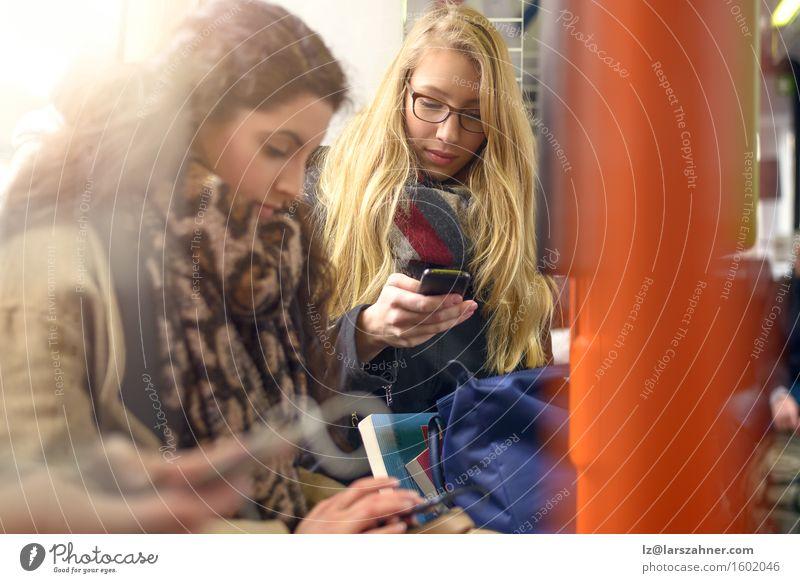 Mensch Frau Jugendliche 18-30 Jahre Erwachsene Freundschaft Textfreiraum modern blond sitzen Technik & Technologie lesen Telefon brünett Entwurf PDA