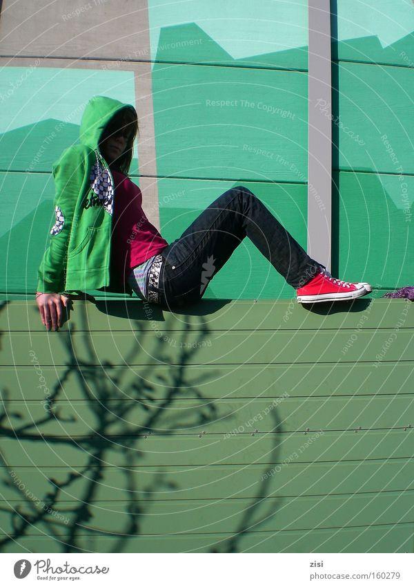 Lärmschutzwand Frau grün Einsamkeit Wand Mauer Erwachsene sitzen modern Coolness Jeanshose Schuhe Chucks Turnschuh Subkultur unerkannt Kapuzenpullover