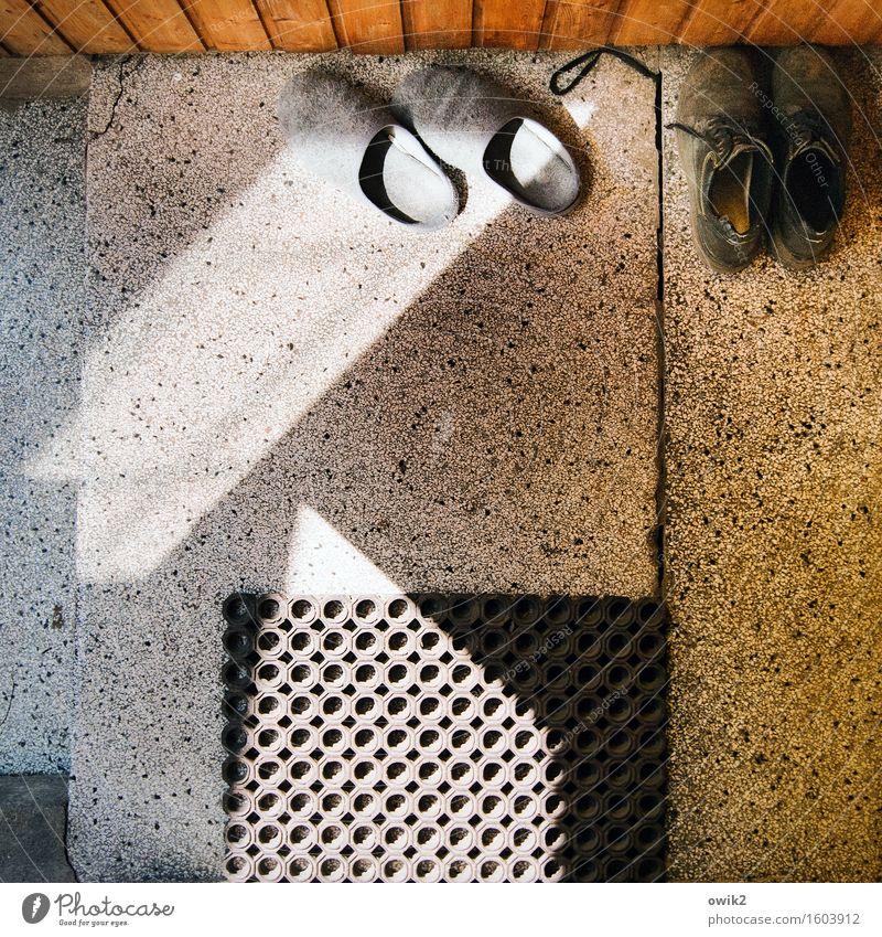Zwei Paar Schuhe Hausschuhe paarweise Fußmatte Gummi Terrakotta Fußboden Stein Holz Kunststoff warten unten Gelassenheit geduldig ruhig Lichteinfall Feierabend