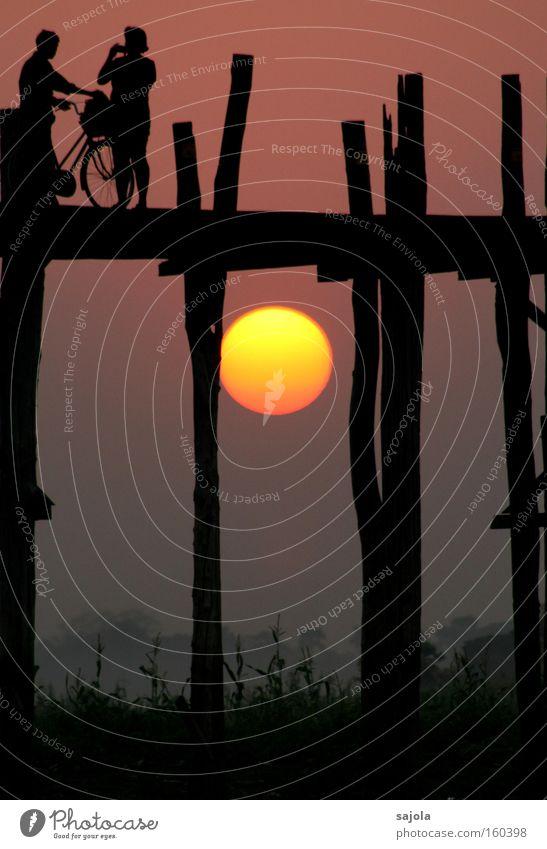 silhouetten vor glühender sonne Mensch schön Sonne Ferien & Urlaub & Reisen gelb Silhouette Stimmung Fahrrad Brücke Sonnenuntergang ästhetisch Abenteuer
