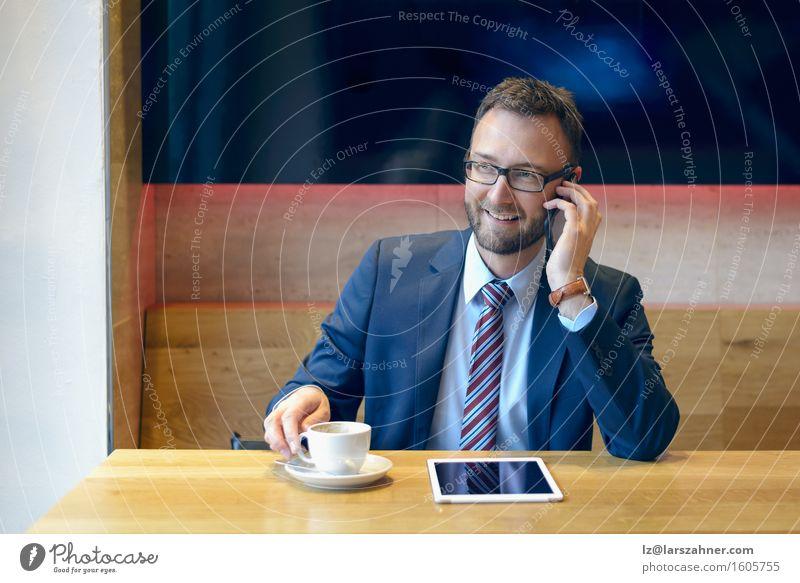 Hübscher Geschäftsmann in der Klage, die einen Handy verwendet Kaffee Arbeit & Erwerbstätigkeit Business Telefon Technik & Technologie Mann Erwachsene Anzug
