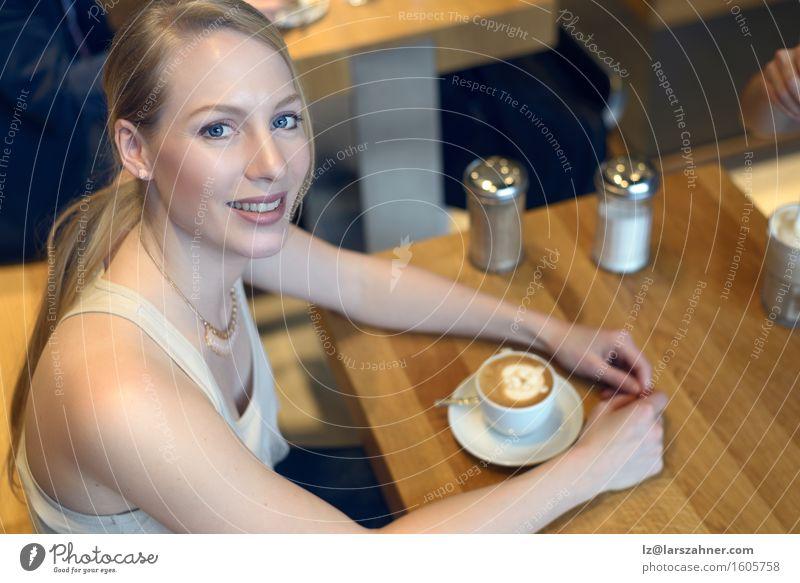 Lächelnde blonde Frau, die in einer Bar mit einem Cappuccino sitzt Mensch Jugendliche schön Erholung 18-30 Jahre Erwachsene feminin Lifestyle oben Textfreiraum