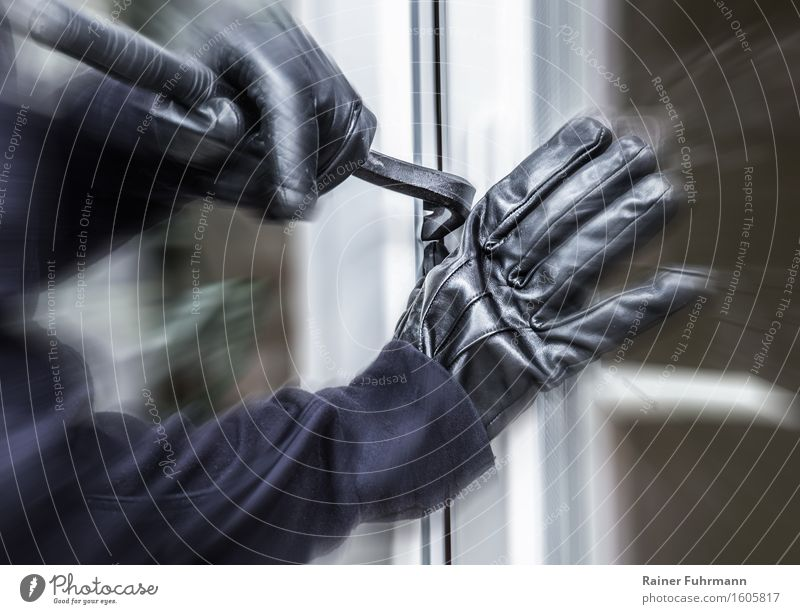 Ein Einbrecher hebelt ein Fenster auf Mensch Angst Arme gefährlich bedrohlich Macht Aggression Zerstörung