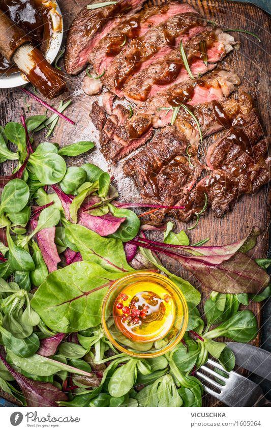 Geschnittenes Steak vom Grill serviert mit grünem Salat Lebensmittel Fleisch Gemüse Salatbeilage Kräuter & Gewürze Öl Ernährung Mittagessen Abendessen Festessen