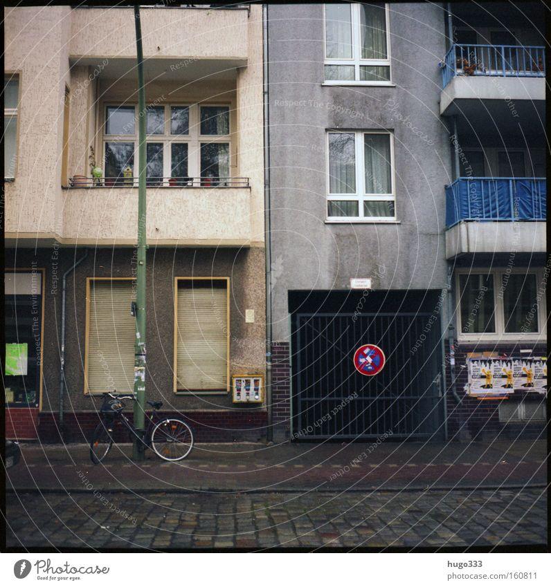 Berlin I Haus Neukölln Schilder & Markierungen Straße Winter Häuserzeile Fahrradweg Kopfsteinpflaster Balkon trist Fenster Rollladen Ausfahrt Verkehrswege