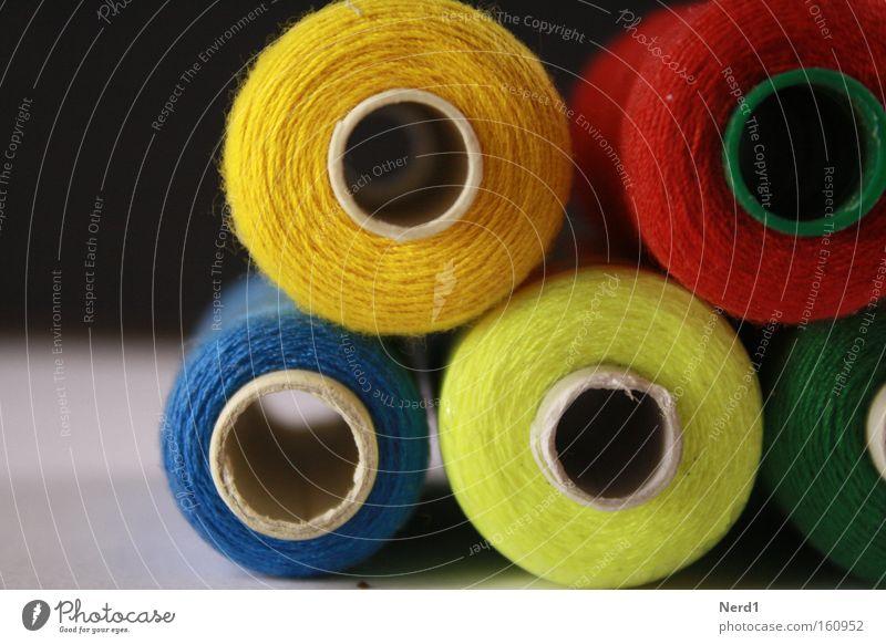 Stapelverarbeitung. Nähgarn Farbe mehrfarbig Rolle Loch blau rot gelb gerollt aufeinander rund Bildausschnitt Anschnitt Detailaufnahme Hintergrund neutral