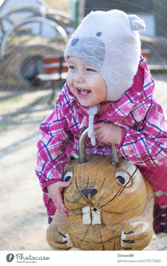 Ride on a hamster feminin Kind Kleinkind Mädchen Kindheit 1 Mensch 1-3 Jahre Abenteuer Freude Mütze Spielplatz Reiten lachen grinsen Farbfoto Außenaufnahme Tag