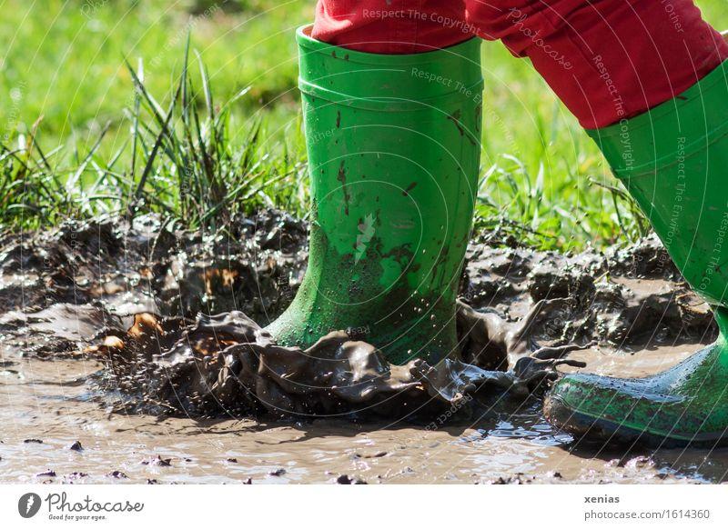 Grüne Gummistiefel platschen in matschige Pfütze Schlamm Matsch Spielen Kind Fuß Mensch Wasser Wassertropfen Wiese springen dreckig nass braun grün rot Freude