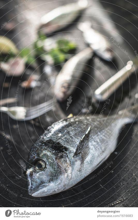 Rohe Seebrassenfische auf Dunkelheit Meeresfrüchte Mittagessen Abendessen Diät Gastronomie Holz dunkel frisch lecker schwarz weiß roh Goldbrasse geschmackvoll