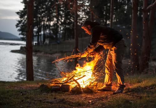Mann beleuchtet ein Feuer im Kamin in der Natur nachts Mensch Ferien & Urlaub & Reisen Sommer Baum Wald Berge u. Gebirge Erwachsene Wärme natürlich hell