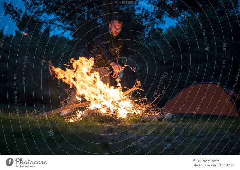 Mann beleuchtet ein Feuer im Kamin in der Natur nachts Freizeit & Hobby Ferien & Urlaub & Reisen Tourismus Abenteuer Camping Sommer Berge u. Gebirge wandern