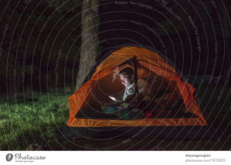 Mann, der seinen Smartphone in einem Zelt aufpasst Mensch Ferien & Urlaub & Reisen Sommer dunkel Wald Erwachsene Lifestyle Glück Freundschaft wandern Aktion