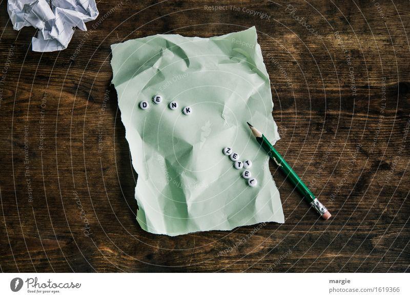 """Die Buchstaben """"Denk Zettel"""" auf einem grünen zerknüllten Blatt Papier und Bleistift auf einem Holztisch Bildung Schule lernen Berufsausbildung Büroarbeit"""