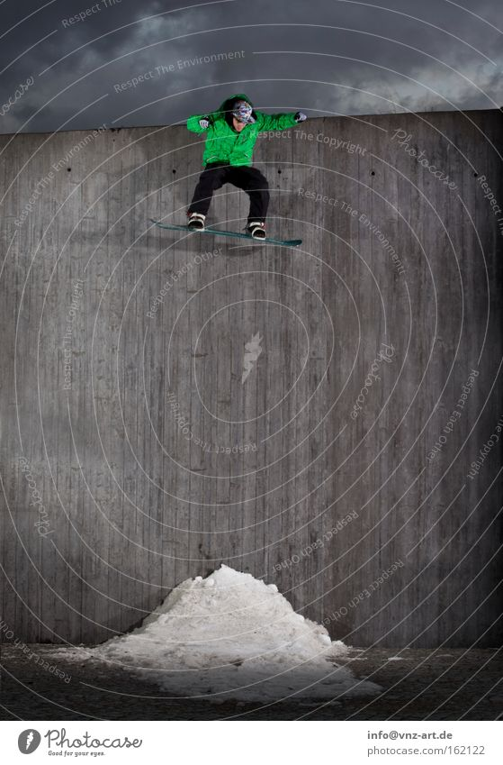 Bombdrop Snowboard Aktion Sport extrem springen Winter grün Wand Extremsport Drop fallen Schneehaufen hoch Mut gewagt Betonwand neongrün grau graue Wolken
