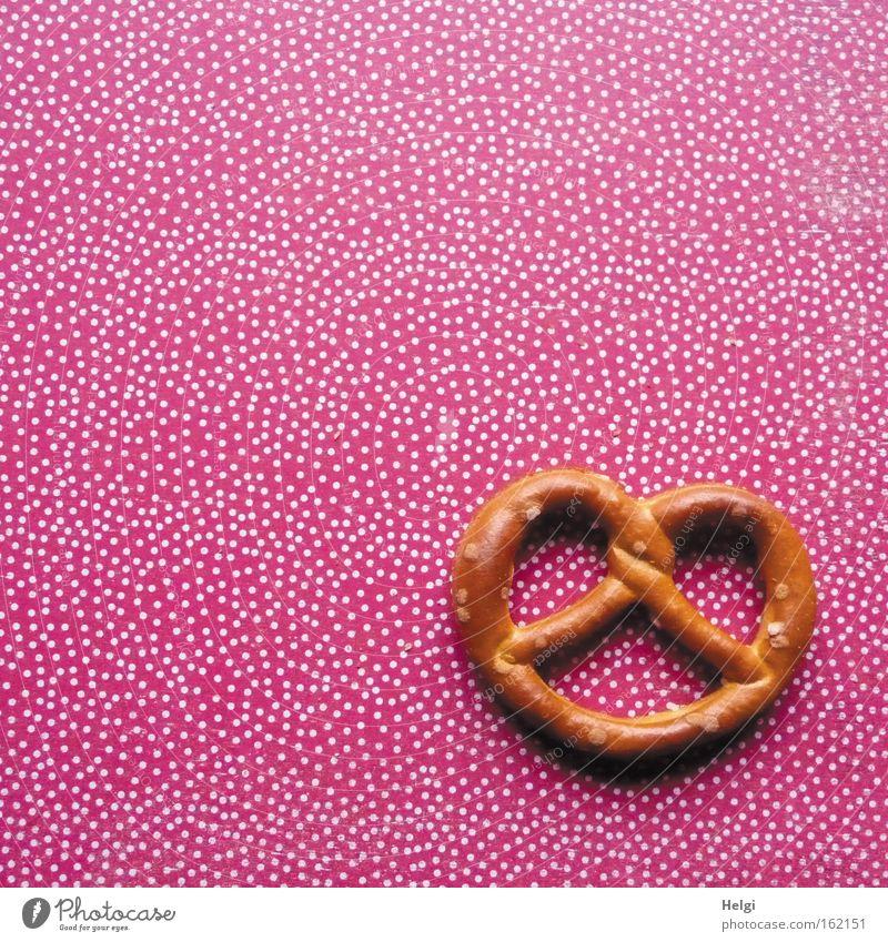 eine Salzbrezel liegt auf einem Hintergrund mit rot-weißen Punkten Brezel Backwaren Ernährung Knabbereien salzig Feste & Feiern lecker braun Club
