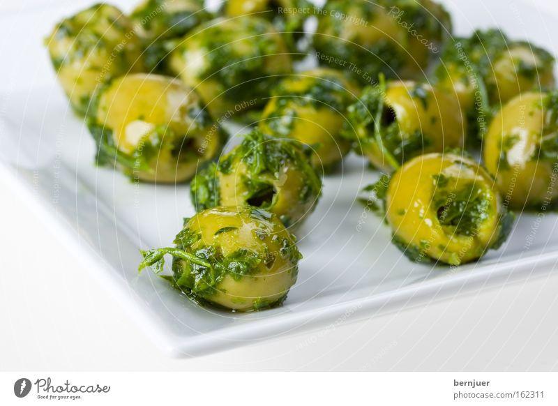 Oliven auf einem eckigen Teller Kräuter & Gewürze Snack Vorspeise Ernährung eingelegt kernlos entkernt