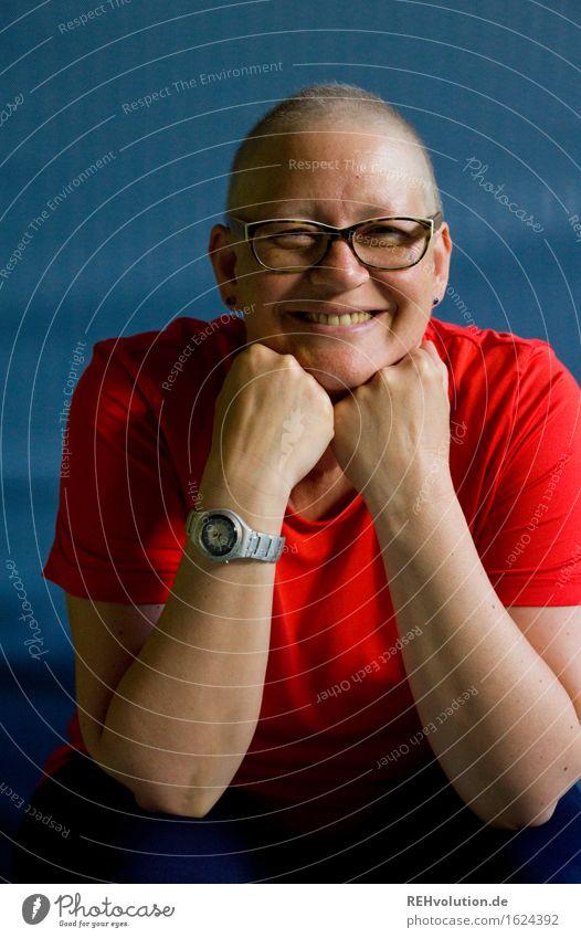 susi sorglos Mensch feminin Frau Erwachsene 1 30-45 Jahre Brille Glatze Lächeln sitzen authentisch außergewöhnlich Coolness sportlich blau rot Freude Glück