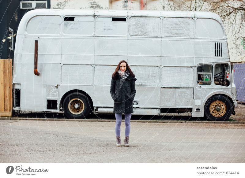 Junge Frau steht vor einem Bus Lifestyle Stil Winter feminin Jugendliche Erwachsene 1 Mensch 18-30 Jahre Stadt Straße Jacke Mantel Stiefel brünett Lächeln