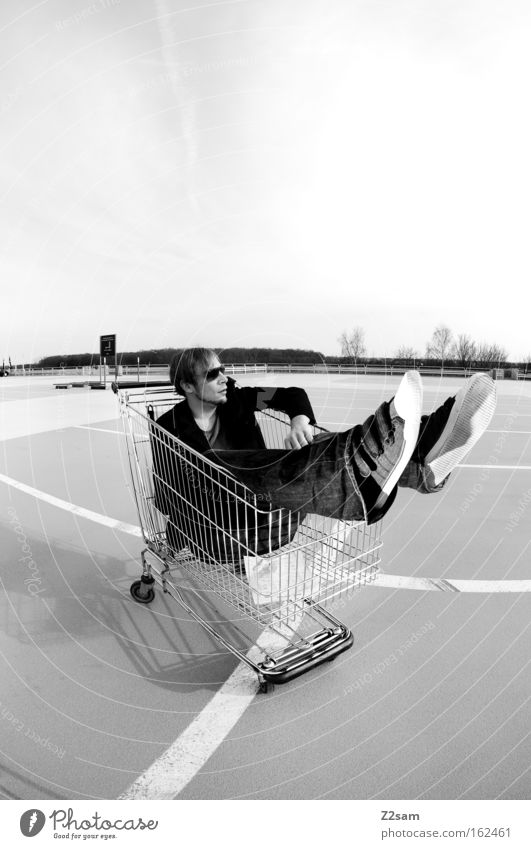 Sonderangebot Mensch Mann Linie sitzen Coolness Parkplatz lässig Einkaufswagen Schwarzweißfoto