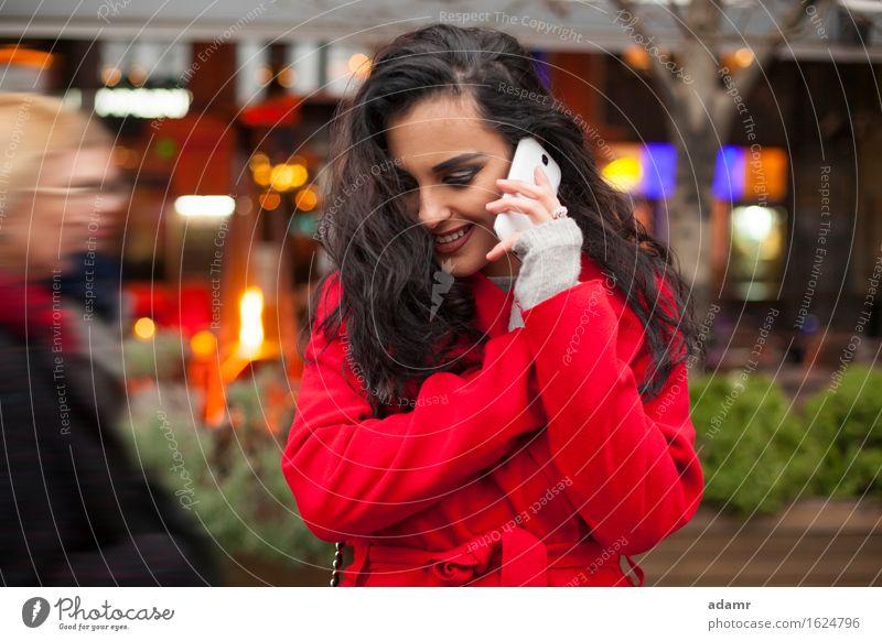 Frau in rotem Mantel mit Handy in der Hand, Smartphone, Stadtszene Telefon Lächeln Lifestyle Mädchen Mobile Person kalt Winter Technik & Technologie Zelle