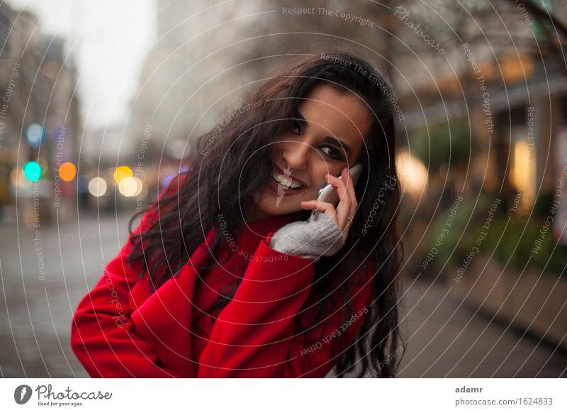 Schöne lächelnde Frau in rotem Mantel mit Mobiltelefon in der Hand, Smartphone, Stadtszene Telefon Lächeln Lifestyle Mädchen Mobile Person kalt Winter
