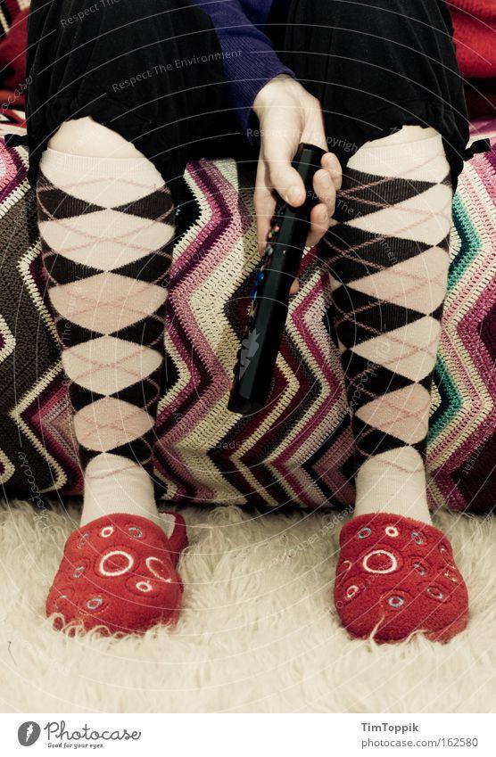 Ein Kessel Buntes mehrfarbig Schuhe Fernseher Fernsehen Wohnzimmer Langeweile Strümpfe Teppich Fernsehen schauen Hausschuhe Medien Fernbedienung geschmacklos Flokati Stubenhocker